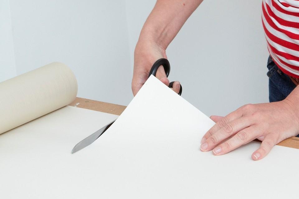 Отрежьте полосу обоев ножницами или оформительским ножом