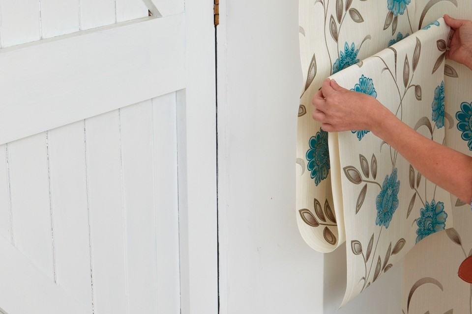 Наклейте обои через внешний вертикальный край дверной рамы с небольшим припуском, припуск сразу же разгладьте или обрежьте