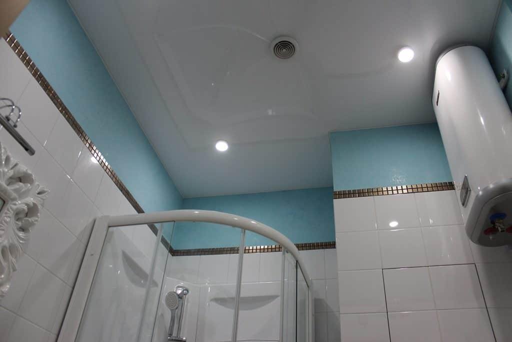 Белый натяжной потолок, в центре установлена вытяжка