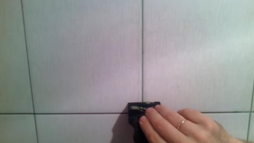 Выравнивание затирки резиновым шпателем