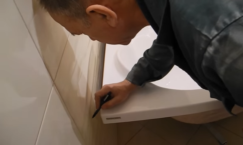 Мастер делает разметку на стене