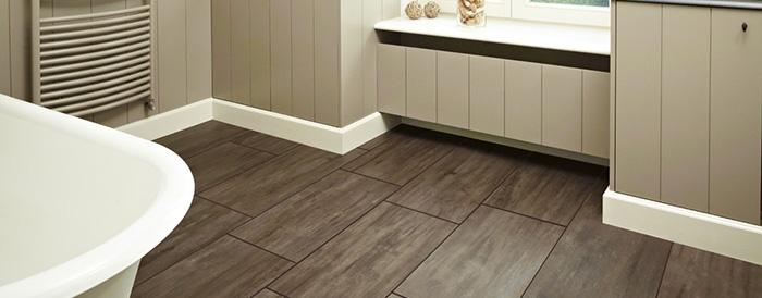 На фото ПВХ плитка на полу в ванной комнате, рисунок - имитация  дерева