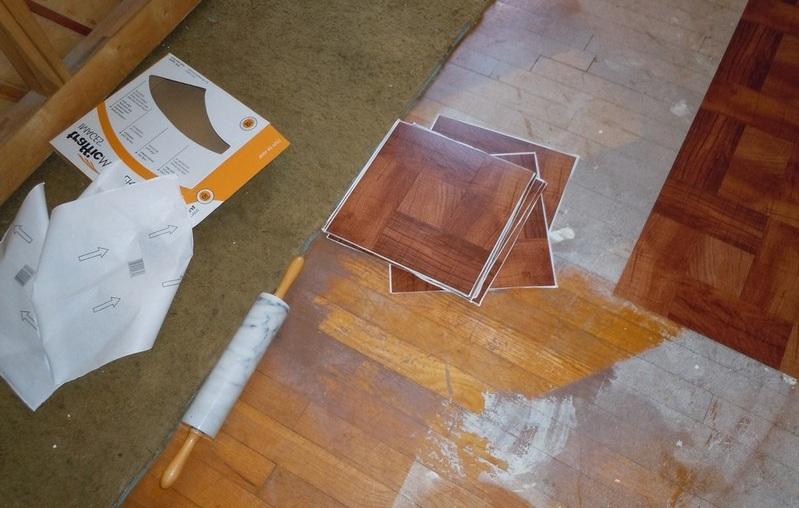 Самоклеящаяся плитка укладывается в два счета. Достаточно снять защитную пленку с изнаночной стороны и прижать плитку к полу