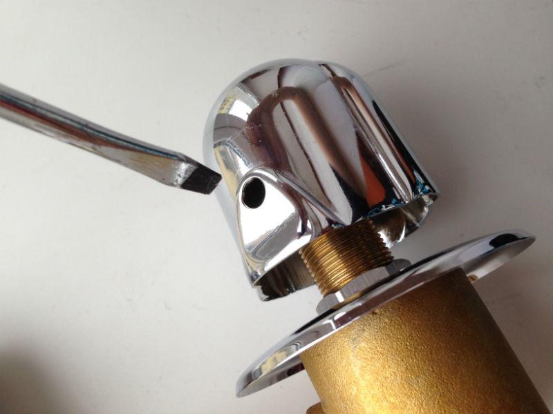 Отверткой откручиваем маленький винт в отверстии ручки и снимаем ее