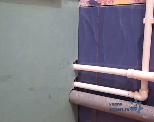 В листе гипсокартона вырезаны отверстия под трубы