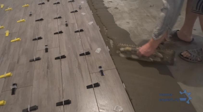 Выравнивание налитого на пол клея шпателем