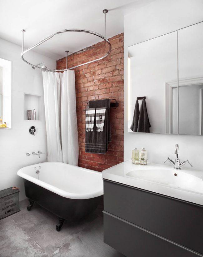 Чугунная ванна с овальным карнизом на фоне кирпичной кладки