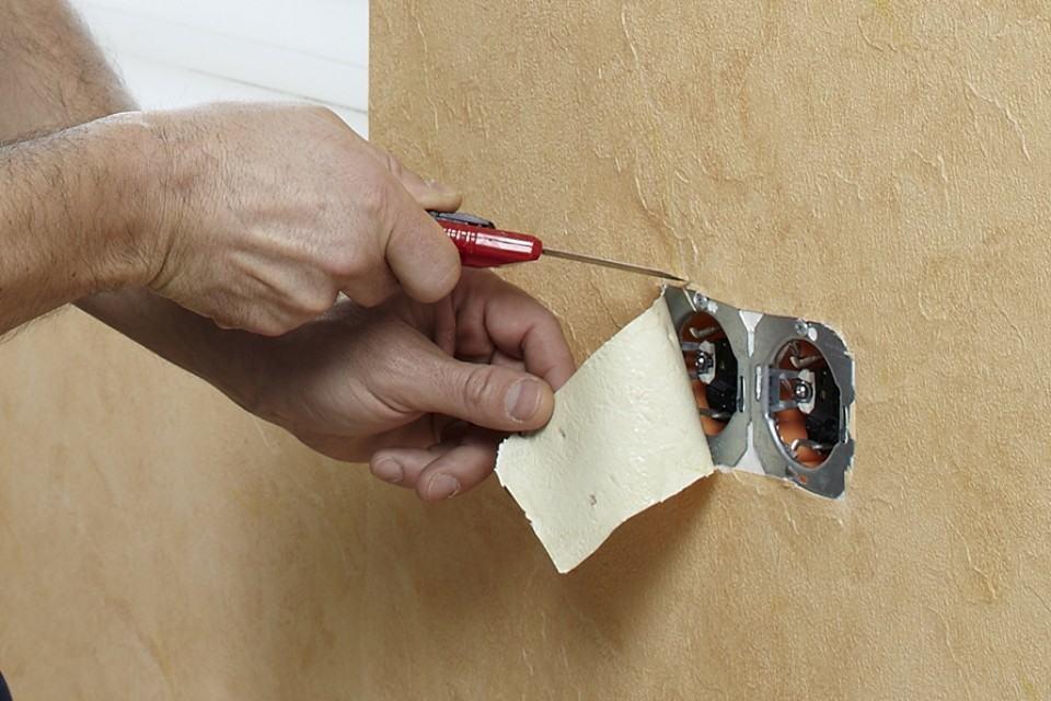 Без нажима накройте выключатель обоями и сделайте диагональный разрез через него. Осторожно вырежьте края и прижмите обои к стене