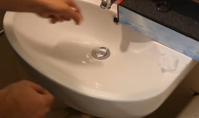 Вставьте трубку со сливной решеткой или кнопкой, как на фото, в отверстие раковины