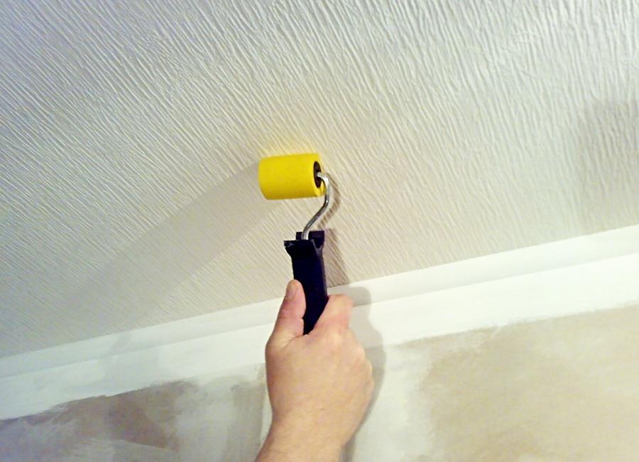 Выдавливание воздуха валиком из-под обоев на потолке