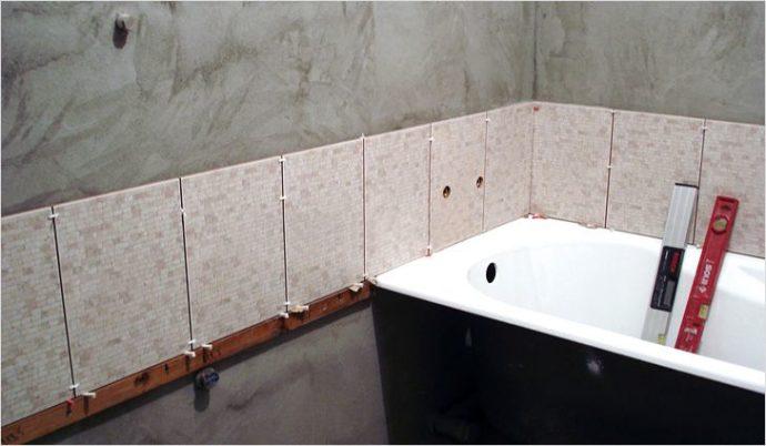 На фото показан пример укладки первого ряда плитки над бортом ванны