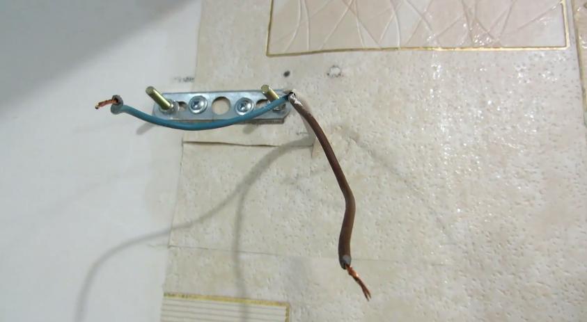 На фото показано, как мастер прикрепил к сетен монтажную планку и вывел электрические провода