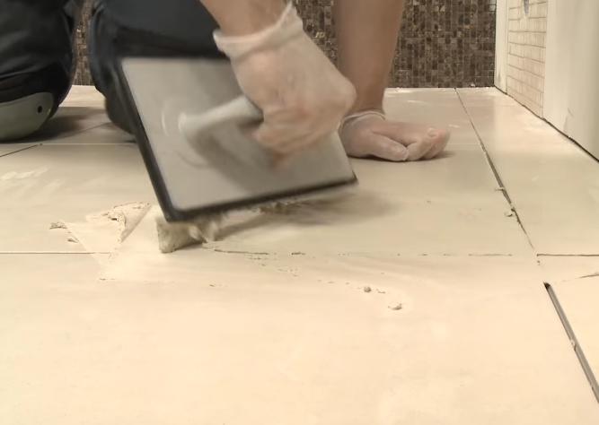 Нанесение затирки на плиточные швы на полу