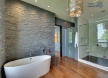 Эффектный интерьер просторной ванной комнаты с отделкой стен камнем