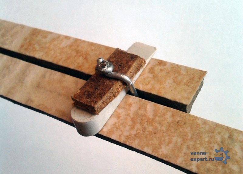 Сверху проволока скручивается и вставляется обычный пластиковый клин от плитки и подкладка из ДВП
